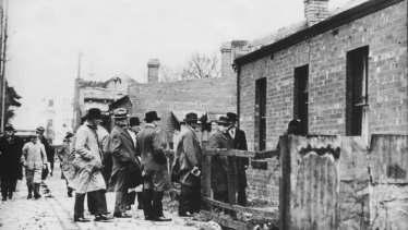 Premier Albert Dunstan and members of the Parliamentary party inspect a dilapidated house in Collingwood.