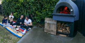 Sandra and Gianluca Bocci with their daughters Chloe (13) Astrid (11) fire up their wood-fire pizza oven in backyard.