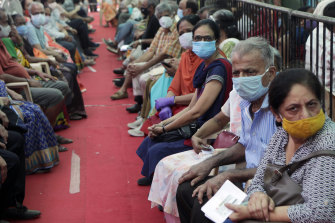 People wait to receive COVID-19 vaccine in Mumbai, India, on Thursday. Several states have reported running out of vaccine doses.