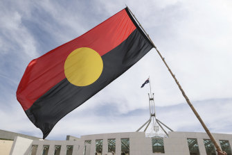 The Aboriginal flag is seen during a protest last month by Indigenous Australians on the forecourt of Parliament House in Canberra. Glen Eira Council will fly its Aboriginal and Torres Strait Islander flags at half mast on Australia Day.
