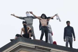 Inmates stand on the roof of the San Vittore prison to protest new coronavirus restrictions.