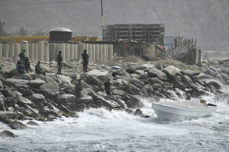 Security forces guard the shore area and a boat in which authorities claim a group of armed men landed in the port city of La Guaira, Venezuela.