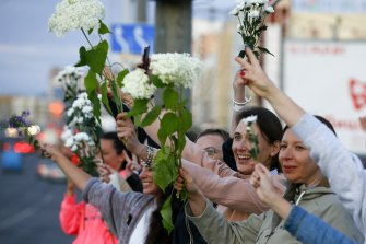 Women wave flowers as they join protest against the Belarus election results on August 13.