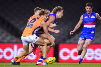 Aaron Naughton collects Lachie Whitfield. The GWS star suffered concussion.