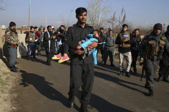 An Afghan security policeman carries his injured daughter after an attack near the US Bagram Air Base in Kabul.