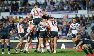 What a win: The Tigers celebrate their victory in golden point time after a field goal by Benji Marshall.