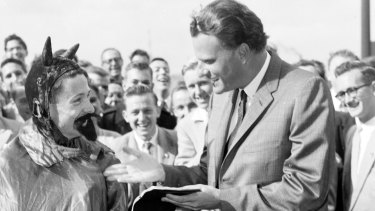 Approachable: Billy Graham speaks to a person dressed as the devil before preaching to students at the University of Sydney in May 1959.