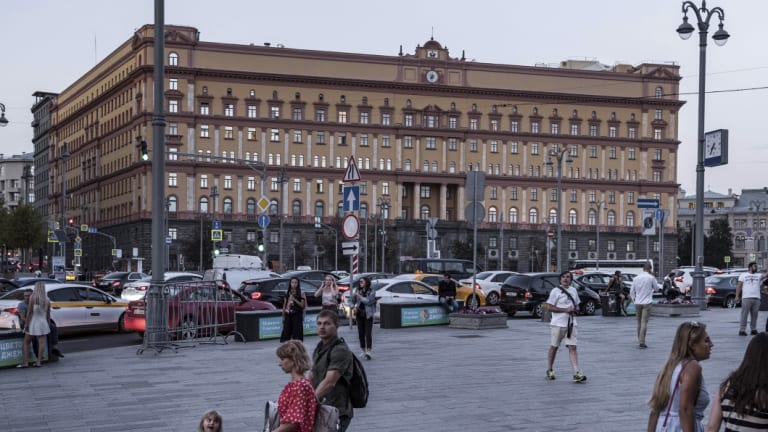 People walk at Lubyanka Square with the building of the Federal Security Service, the successor the KGB in in Moscow.