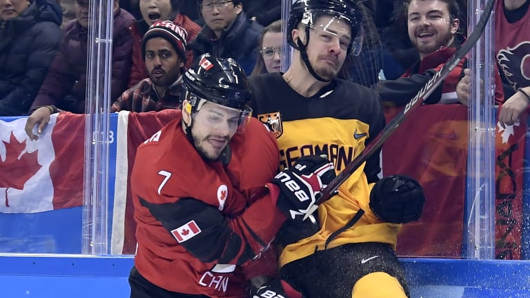 Canada forward Gilbert Brule checks Germany defenceman Moritz Muller into the boards.