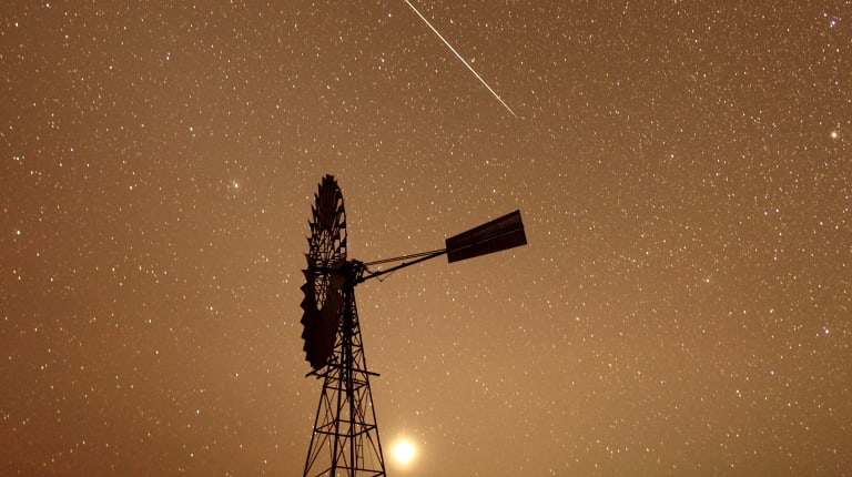 A meteor burns up in the atmosphere over the Spell Bore Yards on Newcastle Waters Station in the NT's west Barkly region as part of the annual Geminoid meteor shower.
