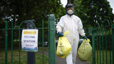 A city council worker carries rubbish from a coronavirus testing centre at Spinney Park in Leicester.