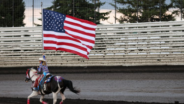 A sense of relief may be premature: a woman on horseback carries an American flag during the national anthem prior to a NASCAR event in in Knoxville, Iowa.