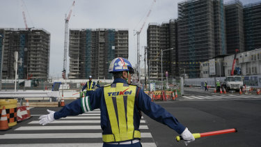 A guard directs traffic at the construction site of the Tokyo Olympic Village last year. Tokyo's governor is considering the possibility of using the unfinished Olympic Athletes Village as a temporary hospital for coronavirus infected patients.