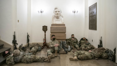Members of the National Guard rest under a bust of Abraham Lincoln in a hallway of the US Capitol building in Washington ahead of Donald Trump's second impeachment vote.