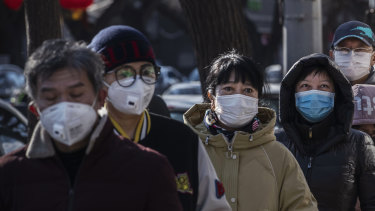 Chinese customers wear protective masks as they line up single file to buy dumplings at a popular local shop in Beijing, China.