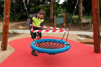 A Willoughby Council worker places hazard tape on outdoor playground equipment at Gore Hill.