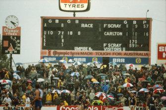Spectators huddle under umbrellas as the rain pours down.