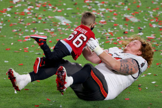 Ryan Jensen celebrates with his child after defeating the Kansas City Chiefs in Super Bowl LV.