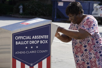 A voter drops her ballot off during early voting on Tuesday AEDT in Athens, Georgia, US.