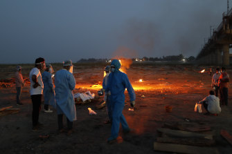 Relatives stand near the funeral pyre of a loved one who died due to COVID-19 in Prayagraj, India.