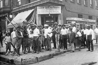 A crowd of men and armed National Guard stand in front of the Ogden Cafe during race riots in Chicago in the Red Summer of 1919.