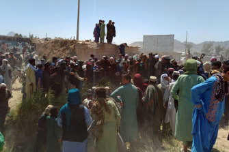Taliban fighters and Afghans gather around the body of a member of the security forces who was killed in the city of Farah on Wednesday.