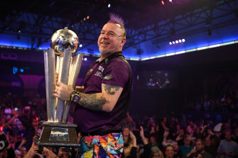 Peter 'Snakebite' Wright lifts the Sid Waddell trophy after seeing off  Michael van Gerwen in the world championship final.