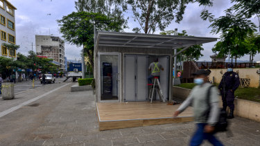 A worker installs a Chivo Bitcoin automated teller machine booth at Gerardo Barrios plaza in San Salvador.