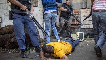 A man lies on the ground after being arrested in Jeppe's Town, Johannesburg, on Tuesday.