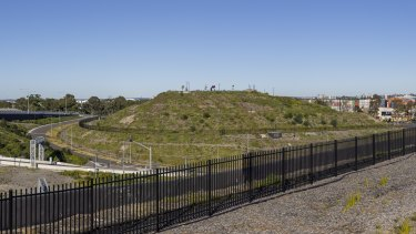 The fenced-off hill at the south-western end of the motorway interchange dominates the area.