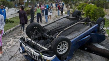 A car overturned by the tornado lays smashed on top of a street pole in Havana.