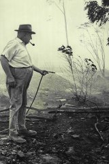 Mr. Arthur Hoskins uses a garden hose outside his home at the height of the bushfires on November 27, 1968.
