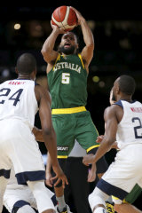Patty Mills rises above USA's defence to fire off a shot for Australia.