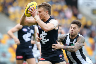 Caught short: Carlton's Patrick Cripps tries to evade a tackle from Collingwood's Jamie Elliott.