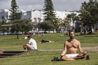 A man takes some time to meditate at Bondi Beach, Sydney on Friday.