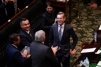 NSW Treasurer Dominic Perrottet is congratulated by Health Minister Brad Hazzard on Tuesday after reading his annual budget speech.