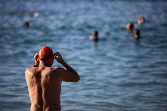 A man prepares to take to the water at Coogee Beach on Saturday morning.