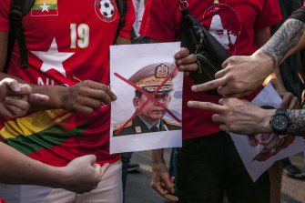 Supporters of Suu Kyi's National League for Democracy point to a crossed-out portrait of Myanmar's army chief, Min Aung Hlaing, at a protest in Bangkok on February 1.