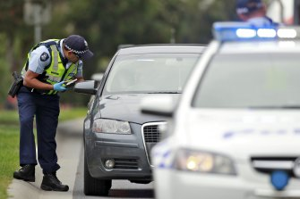 A police officer conducts a random breath test.