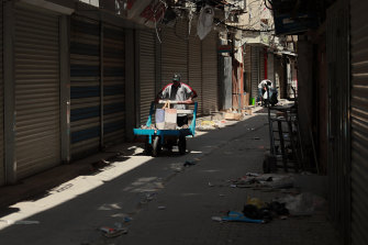 A street vendor pushes his cart an almost empty market during a curfew to help fight the spread of the coronavirus, in Baghdad, Iraq.