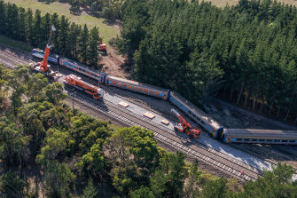 Cranes lifting part of the derailed train at Wallan on Sunday.