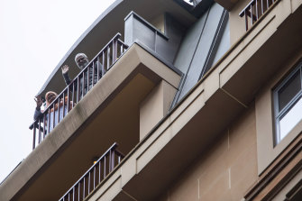Maruf Ahmed's parents in quarantine wave from the top balcony of the Raddison Blu in Sydney's CBD on Saturday.