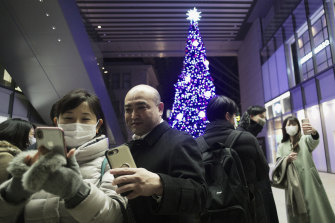 Japanese shopgoers pose for selfies on Christmas Day in Tokyo.