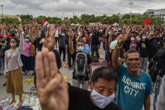 Anti-government protestors hold up a three finger salute during a rally at Sanam Luang on Sunday.