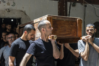 Mourners carry the coffin of Israeli Arab Khalil Awaad and his daughter Nadine,16,  during their funeral in the village of Dahmash near the mixed Israeli city of Lod.