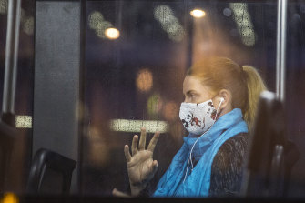 A woman wears a mask on a bus at Parramatta to protect against the spread of COVID-19.