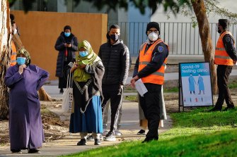 Residents from the Flemington public housing towers at 130 Racecourse Road queue at a makeshift COVID-19 testing centre on Saturday.