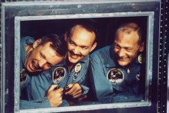 Apollo 11 astronauts (L-R) Aldrin, Collins and Armstrong peering out the window of a quarantine room aboard recovery ship Hornet following splashdown.