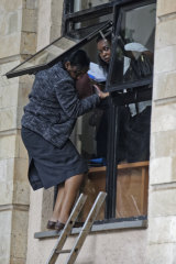 Civilians flee through a window after an attack at a luxury hotel complex in Nairobi.