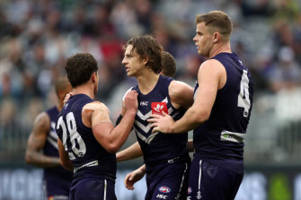 Nat Fyfe of the Dockers celebrates with Lachie Schultz and Sean Darcy after kicking a goal.